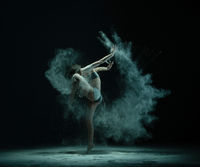 Anonymous dancer throwing sand and lifting leg