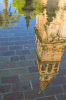 Reflection of the bell tower in a pond inside the inner courtyard of the mosque-cathedral