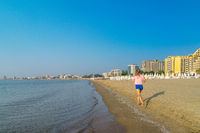 An unidentified woman running in the morning on a beautiful beach in Sunny Beach on the Black Sea coast of Bulgaria