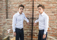 Attractive young man standing against brick wall