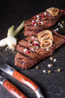 a grilled steak sprinkled with salt and colorful pepper