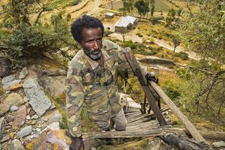 Einheimischer Mann auf der fragilen Holzleiter zur orthodoxen Felsenkirche Petros and Paulos Melehayzengi