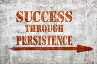 success through persistence  graffiti on stucco wall