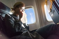Blonde caucasian woman sneezing while traveling by airplane.
