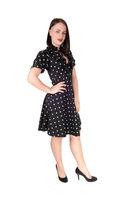 Beautiful woman standing in an pock dot black dress