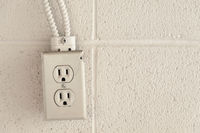 Old rustic North American electrical outlet on a brick wall