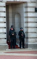Three armed police on Guard at Buckingham Palace