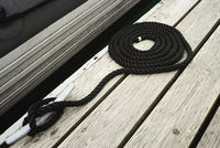 Black Swirled Mooring Rope Tied Up On A Bitt Securing Boat To Jetty