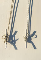 Two nautical ropes tied to metal cleats on wall of cruise ship.