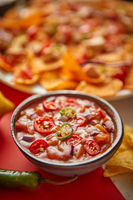 Close up on hot tomato dip in ceramic bowl with various freshly made Mexican foods