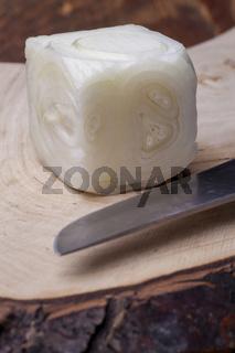 eine Zwiebel in Würfel geschnitten auf Holz