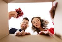 happy couple opening christmas gift box