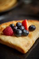 Close up on pancake with fresh fruit topping placed on dark rusty table