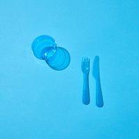 Plastic glass, fork and knife with shadows on a blue table.