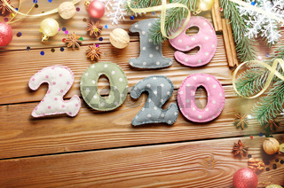 Colorful stitched digits 2019 2020 of polkadot fabric with Christmas decorations flat lyed on wooden background