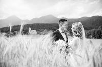Groom hugs bride tenderly in wheat field somewhere in Slovenian countryside.