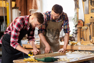 carpenters with ruler and wooden board at workshop