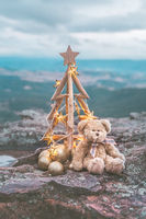 Christmas tree with golden star lights against mountain backdrop