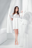 Young beautiful brunette dressed in a white dress.