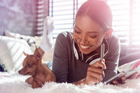 Beautiful smiling girl with headphones and tablet relaxing with her dog on a bed at home