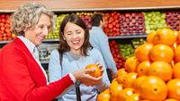 Zwei Frauen prüfen die Frische einer Orange