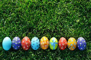 Easter eggs lying on green spring grass arranged in one lane. Space for text