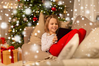 smiling girl with tablet pc at christmas home
