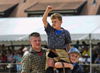 The winner in a children's category in Swiss wrestling on the shoulders of his friends,Switzerland