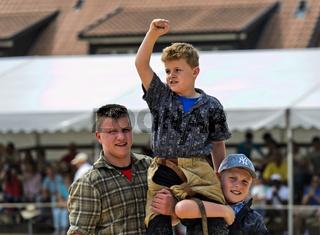 Der Sieger in einer Kinderkategorie auf den Schultern seiner Kameraden