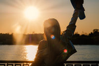 Woman posing with her hands holding skateboard raised up in the sunset sky shot with flares, low contrast image