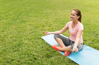 woman meditating on yoga mat at park