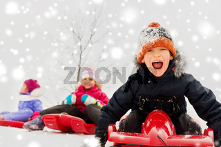 happy kids sliding on sleds in winter