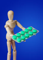Wooden toy figure with pills on blue