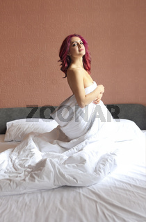 Woman is covering her body with a blanket and looking sensually at camera