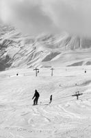 Snowboarders on snowy ski slope and high mountains