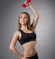 Pretty young fitness trainer with dumbel in studio
