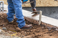 Construction Worker Using Wood Trowel On Wet Cement Forming Coping Around New Pool