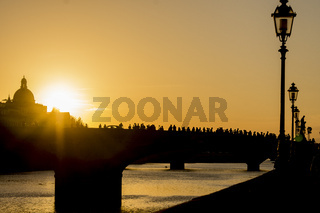 Silhouette of people on bridge during sunset in Florence