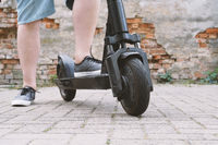 legs of unrecognizable man with electric kick scooter or e-scooter