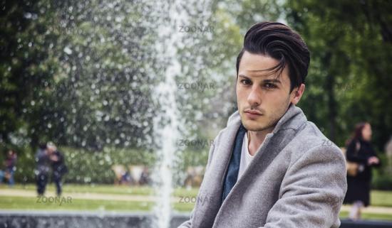 Elegant young man outdoor wearing wool coat