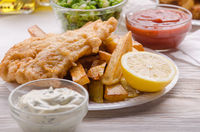 Traditional British street food fish and chips with ketchup and tartar sauces and mushy peas on paper plate