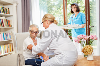 Ärztin und Altenpflegerin kümmern sich um Seniorin