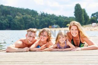 Familie mit Sohn und Tochter auf Steg am See