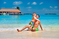 Toddler boy on beach kissing father