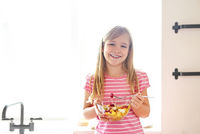 Portrait of the little cute girl eating fresh fruit salad
