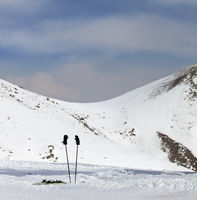 Skiing equipment on snowy ski slope at sunny winter day