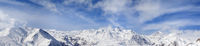 Panorama of winter snowy mountains and blue sky with sunlit clouds