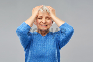 stressed senior woman holding to her head