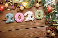 Colorful stitched digits 2020 of polkadot fabric with Christmas decorations flat lyed on wooden background