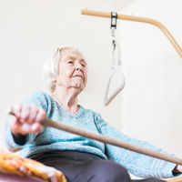 Elderly 96 years old woman exercising with a stick sitting on her bad.